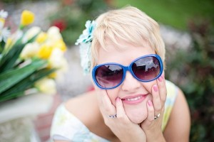 happy woman outside in garden wearing sunglasses