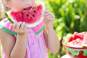 little girl eating watermelon in the summer