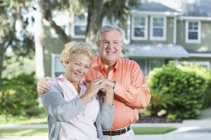 Senior couple standing in front of house.